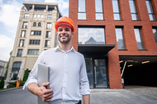 Мужчина-инженер в защитном шлеме стоит возле здания и выглядит позитивно