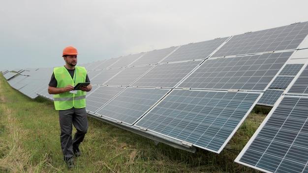 유니폼과 단단한 헬멧을 쓴 남성 엔지니어는 디지털 태블릿을 들고 태양 전지판 설치를 확인하는 재생 에너지 스테이션을 걸어갑니다. 대체 에너지. 청정 에너지 개념입니다.