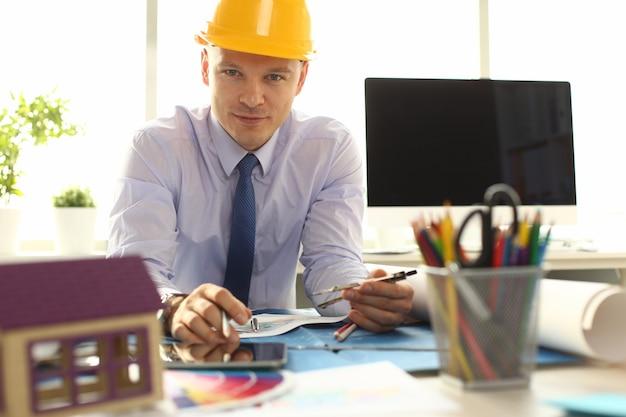 オフィスに座っている黄色いヘルメットの男性エンジニア