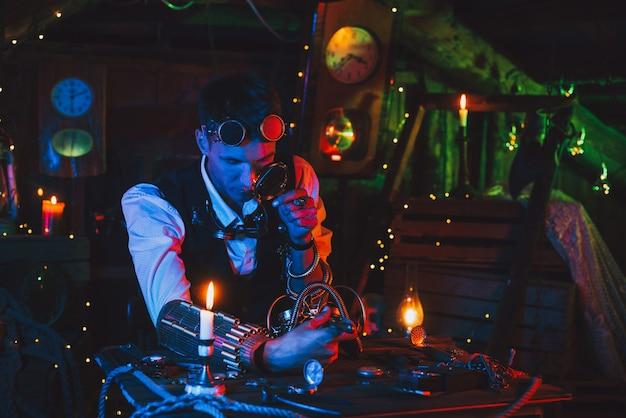Мужчина-инженер-изобретатель ремонтирует фантастический механизм за столом в мастерской