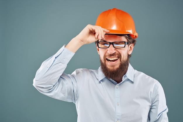 ヘッドスタジオの手のジェスチャーで男性エンジニアオレンジ色のヘルメット