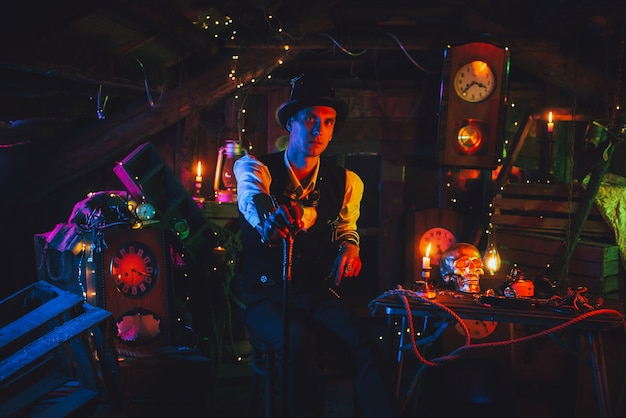 Male engineer in a steampunk suit, a top hat with a cane in his hand is sitting in a watch workshop with a neon light. cyberpunk cosplay