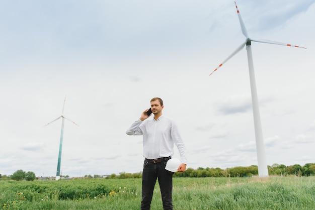 Инженер-мужчина разговаривает по телефону на ветряной электростанции