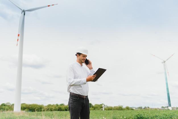 Инженер-мужчина разговаривает по телефону на ветряной электростанции Premium Фотографии