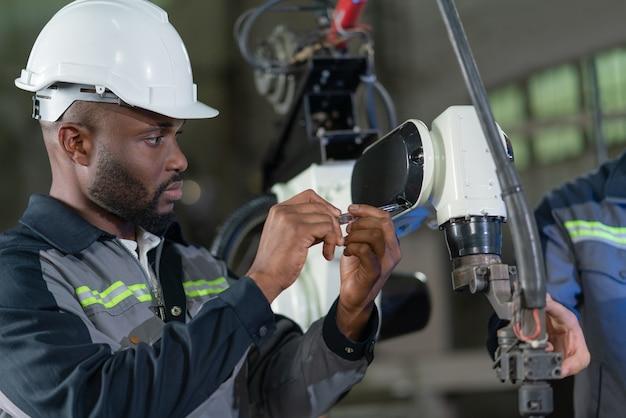 産業工場でドライバー修理ロボットアーム溶接機を使用している男性エンジニア