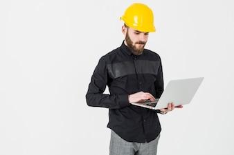 白い背景にラップトップを使用してハードウェアを着ている男性のエンジニア