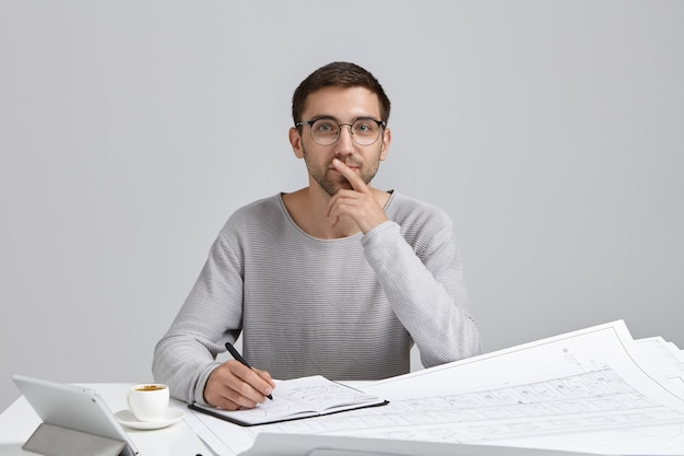 Male engineer wears loose casual sweater and round spectacles, sits at workplace