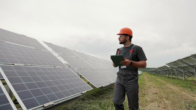 디지털 태블릿 pc를 가진 남성 엔지니어가 현대적인 태양광 패널 근처를 걷고 있습니다. 청정 에너지 생산. 태양광 농장.