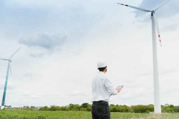 Инженер-мужчина в каске работает на ветряной электростанции на планшете Premium Фотографии