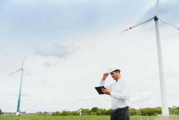 Инженер-мужчина в каске работает на ветряной электростанции на планшете
