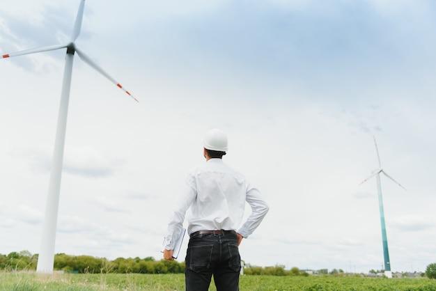 Инженер-мужчина в каске работает на ветряной электростанции Premium Фотографии