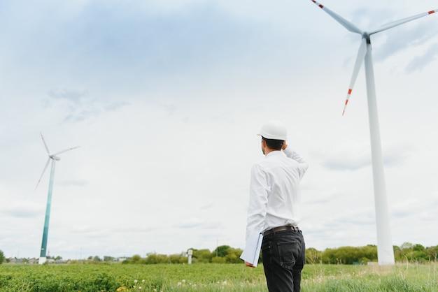 Инженер-мужчина в каске работает на ветряной электростанции