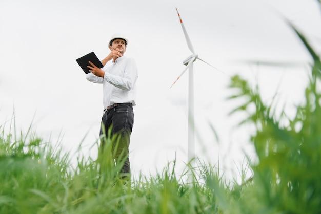 Инженер-мужчина, работающий на ветряной электростанции с планшетом