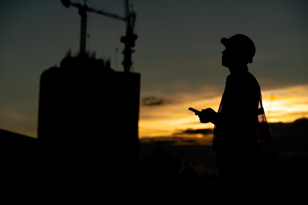 Male engineer working construction site at silhouette sunset time