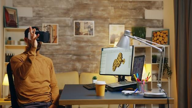 가상 현실 헤드셋을 착용한 기어 시스템을 위한 새로운 기술에 대해 홈 오피스에서 일하는 남성 엔지니어.