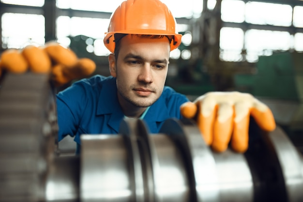 Male engineer works with turbine on factory. industrial production, metalwork engineering, power machines manufacturing