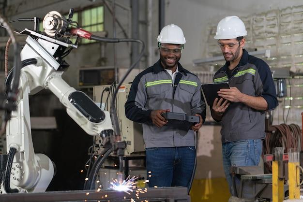 男性エンジニアは、工場でリモコンとタブレットを使用してロボットアーム機械溶接鋼を制御します