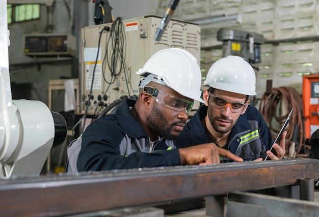 工場でロボットアームマシンで溶接する鋼の溶接を見ている男性エンジニア