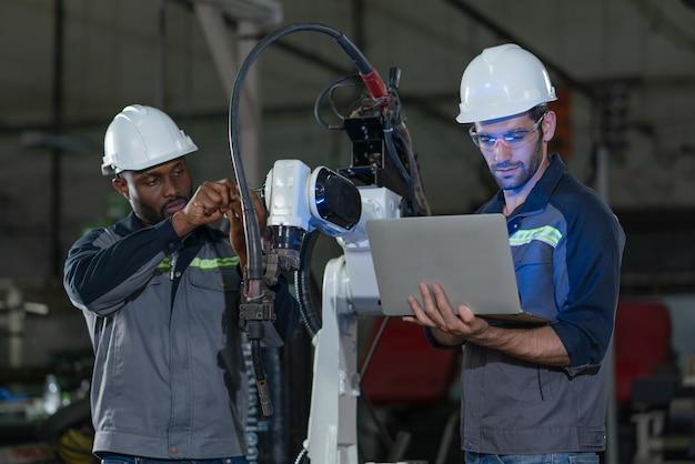 工場でラップトップを備えたロボットアーム溶接機を修理および検査する男性エンジニア