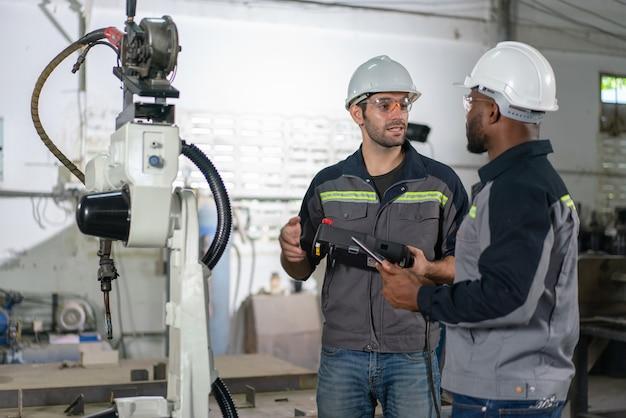 タブレットとリモートコントロールケーブルを使用してロボットアーム溶接機を制御することについて話し合うために立っている男性エンジニアは、産業工場のロボットに接続します。