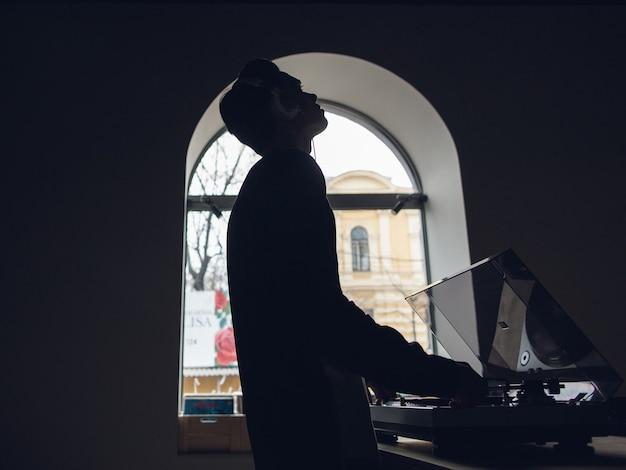 남성은 비닐 레코드에서 음악을 듣는 것을 즐깁니다. 특별한 어두운 분위기의 인테리어, 창의적인 음악 상점, 알아볼 수없는 청취자