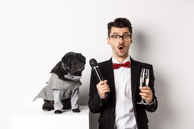흰색 배경 위에 서 있는 귀여운 검은 개에게 마이크를 주고 샴페인 잔을 들고 있는 남성 연예인