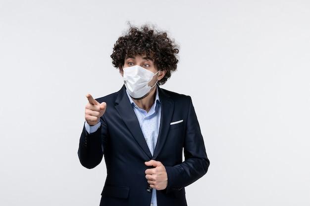 スーツを着て、マスクを着用し、白い表面に何かを指している男性起業家