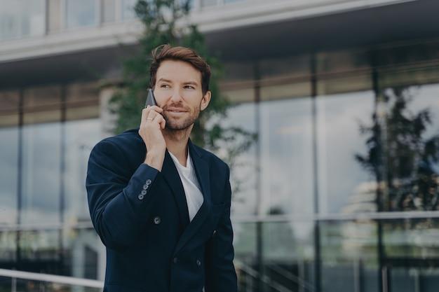 전화를 통한 남성 기업가 대화는 비즈니스 센터 근처에서 긴급한 문제를 해결합니다.