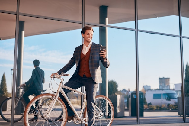 Мужчина-предприниматель с помощью смартфона на велосипеде