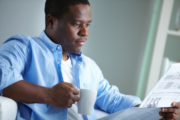 Male executive drinking coffee and reading the newspaper