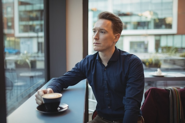 Исполнительный мужчина с кофе за стойкой