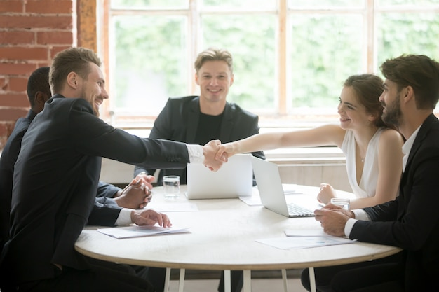 Male executive shaking hands with female coworker, teamwork introduction.