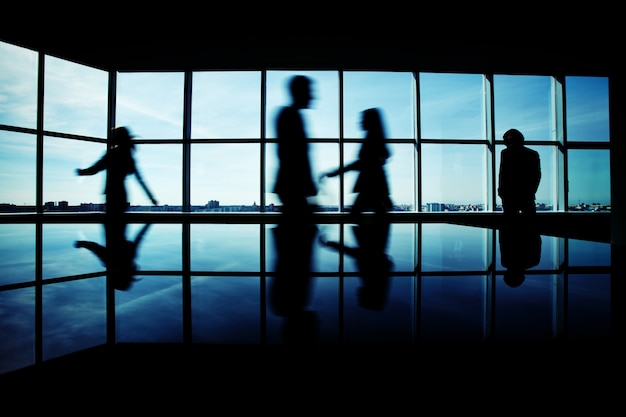 Male executive staring through the window with businesspeople rushing