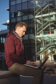 Esecutivo maschio che per mezzo del computer portatile