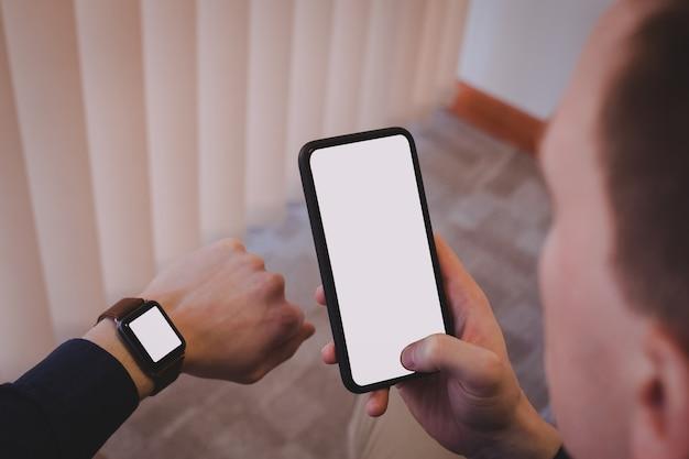 Esecutivo maschio tramite telefono cellulare e controllo del tempo sull'orologio da polso