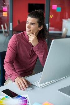 Мужской исполнитель работает на персональном компьютере в офисе