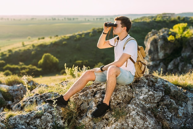 Male explorer sitting on rock looking through binocular