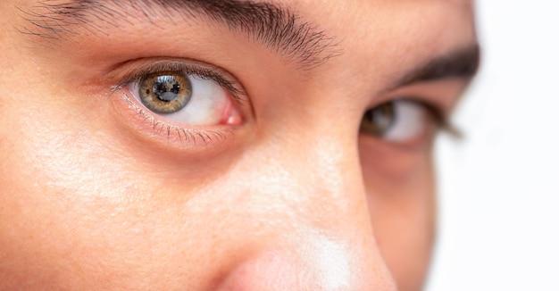 男性の目のクローズアップは白い背景で隔離