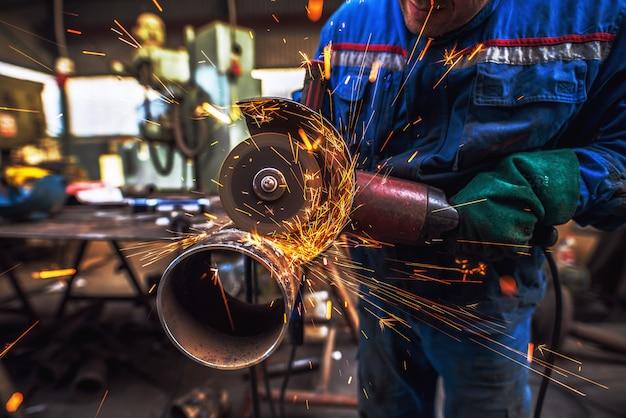 男性の生地労働者がワークショップで電動グラインダーで金属パイプを切断します。