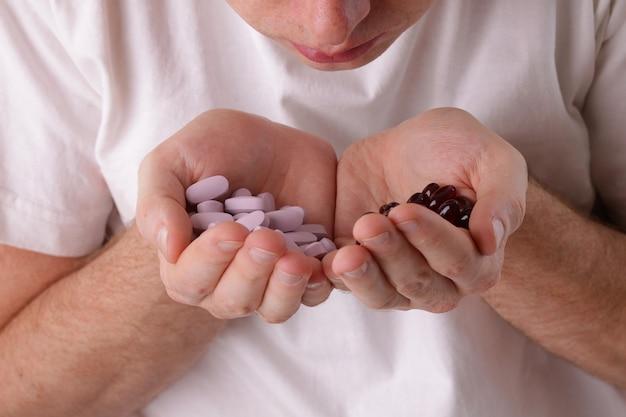 Мужское лицо и таблетки в руках