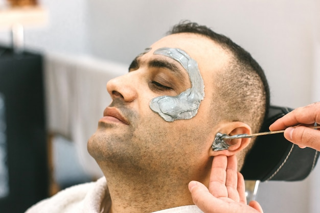 Male face waxing. barber removes hair by shugaring from the face of turkish man.