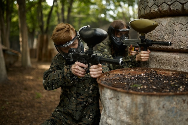 Male and famale warriors in camouflages and masks aimimg with paintball guns