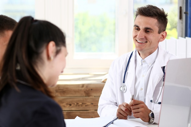 Male family doctor listen carefully young couple in office