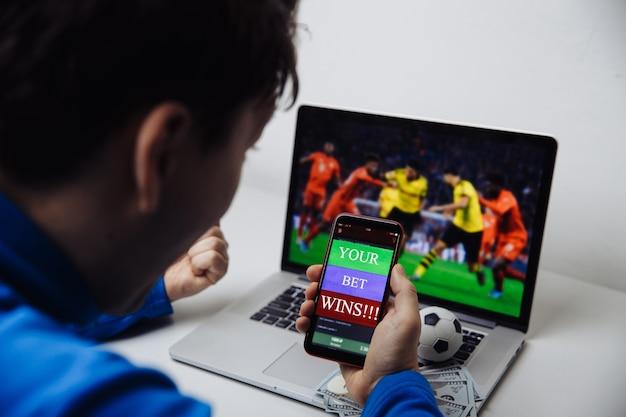 サッカーを見ている男性ファンが彼のラップトップでオンライン放送を再生し、祝う