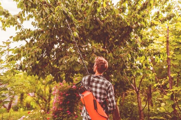Фермер, применяющий спрей-инсектицид на листьях деревьев с помощью насоса