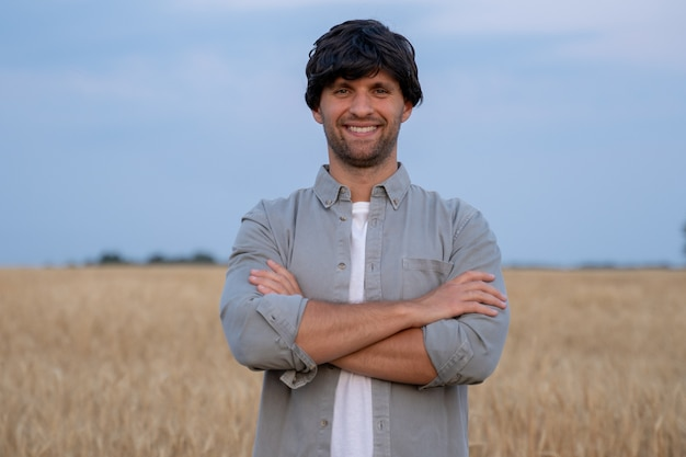 Male farmer crosses his arms and looks at the camera against the background of a wheat field
