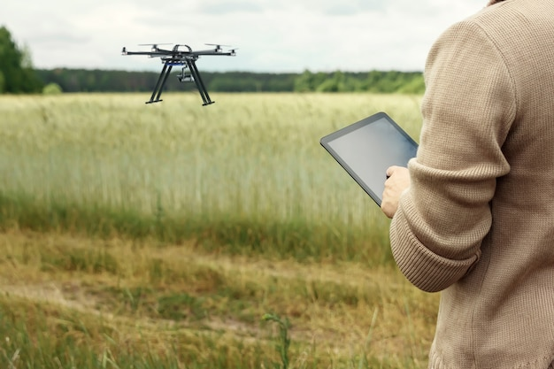 A male farmer manages a drone over agricultural land.