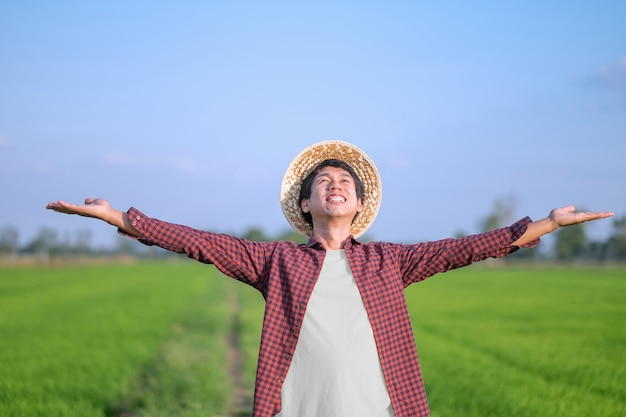 A male farmer in a striped shirt is spreading his arms and smiling happily at a field.
