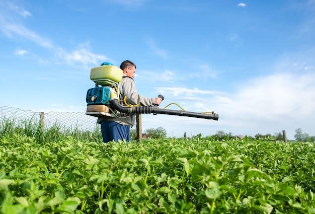 분무기를 가진 남성 농부는 화학 재배 식물로 감자 덤불을 처리합니다