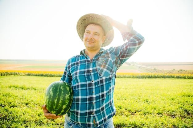 Мужчина-фермер с арбузом в руке, владелец в шляпе в поле дынь в солнечный день